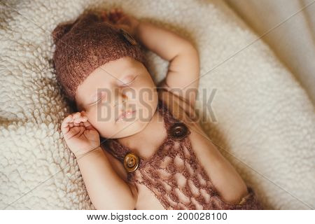 Newborn infant baby boy sleeping on a fluffy blanket. The baby in a knitted hat is sleeping sweetly