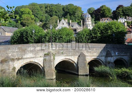 The Old Town Bridge over the river Avon with the bell tower of St Thomas More's Catholic Church in the background, Bradford on Avon, UK