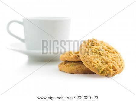 Sweet pistachio cookies and coffee mug. Tasty cookies with pistachio nuts.