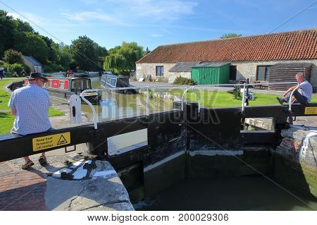 Bradford on Avon, UK - AUGUST 13, 2017: People enjoying a sunny day at Canal Wharf with colorful barges on Kennet and Avon Canal