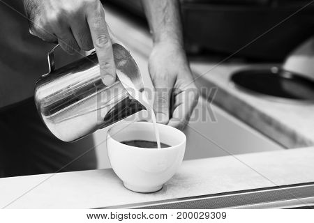 Black and white photo of barista adding milk to the coffee