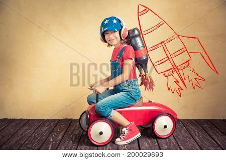 Kid with jet pack driving retro toy car. Child playing at home. Success leader and winner concept