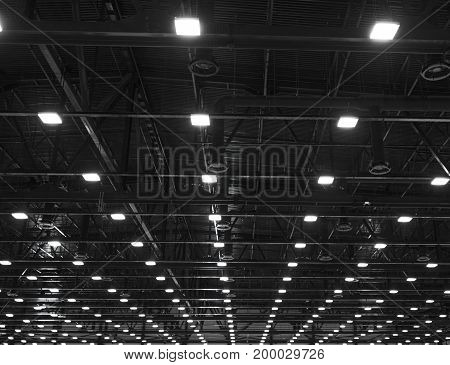 Lights and ventilation system in long line on ceiling of the dark office industrial building exhibition Hall Ceiling construction