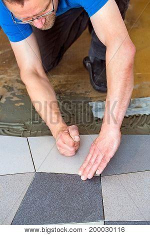 Man Laying Floor Tiles On Adhesive