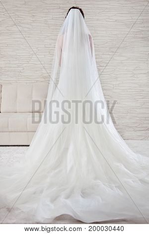 Beautiful wedding and a long white dress, veil, A classic look. Bride standing in white, bright interior.