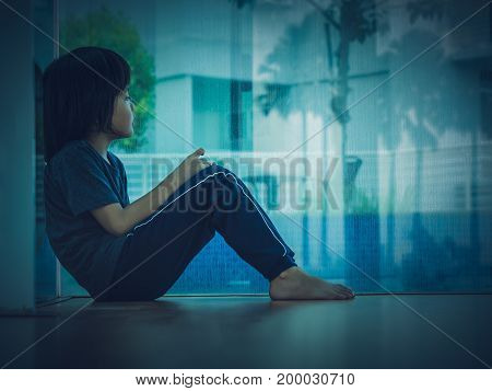 Soft focus little boy unhappy sad stitting in empty room and tress alone. Sad child concept.
