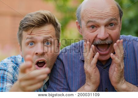 Two shocked men father and son looking at camera with opened mouth. Positive news or win in lottery
