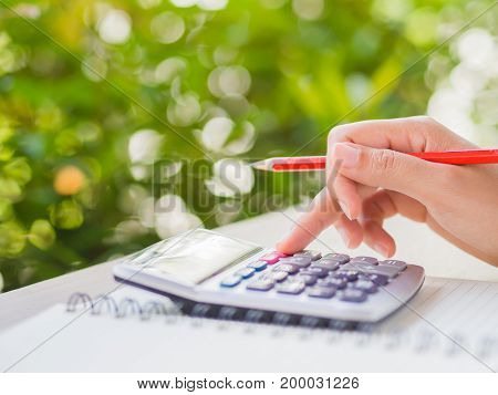 woman hand working with calculator and holding red pencil business document and note book on working table with nature green leaves background.
