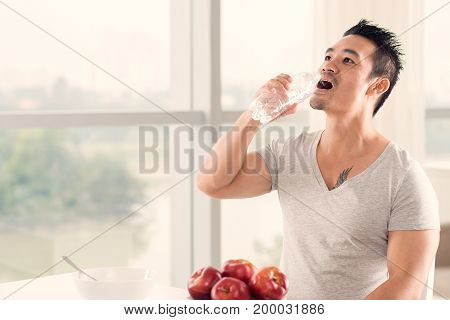 Fit handsome man drinking fresh water in the morning