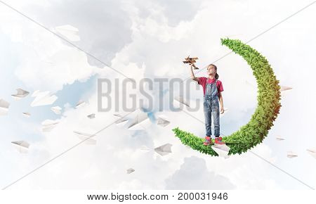 Cute kid girl standing on green moon playing with airplane toy