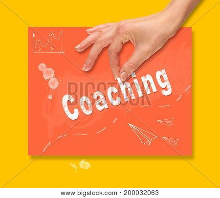 A Hand Picking Up A Coaching Concept On A Colorful Drawing Board.