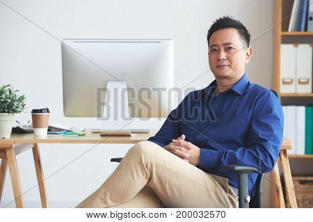 Portrait of confident Singaporean businessman sitting on chair in his office