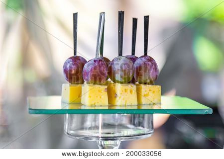 Cheese and plum on a glass stand of the corporate table.