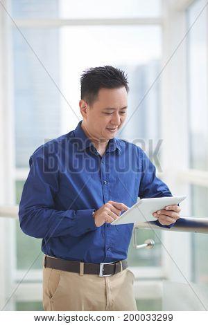 Smiling entrepreneur reading information on tablet computer