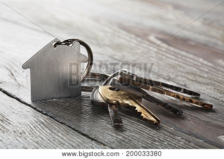 estate concept keychain with house symbol key on wooden background