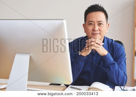 Portrait of smiling businessman sitting at his workplace