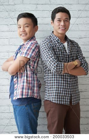 Vietnamese man and his teen son standing with their arms crossed