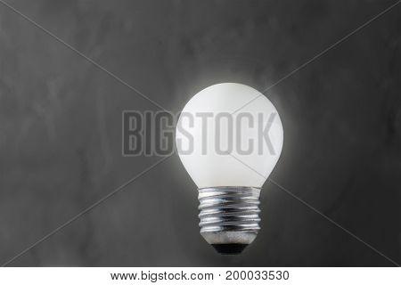 White Light Bulb Glowing On Concrete Background, Idea Concept
