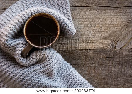 Cup of black coffee wrapped in warm scarf on wooden board. Top view, vintage style. Still life. Flat lay. Copy space.