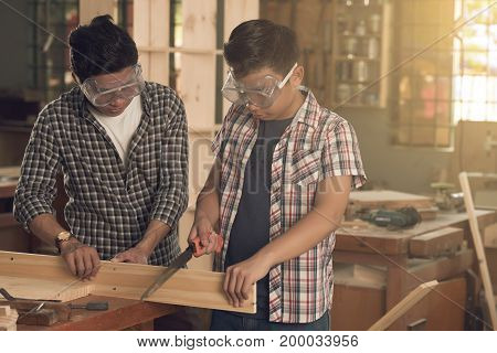 Asian father and son working in joinery together
