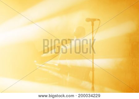 Guitarist silhouette perform on a concert stage. Abstract musical background. Music band with guitar player. Playing guitar and concert concept. Live music, festival background. Instrument on stage