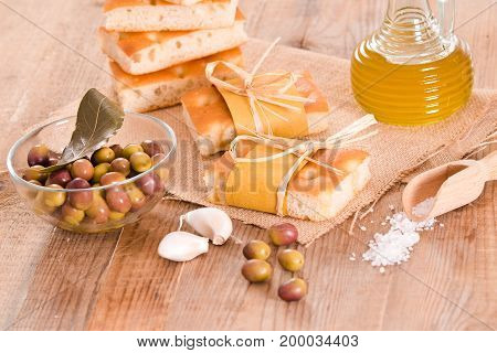 Focaccia bread with olives on wooden table.