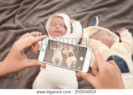 Mother taking photo of cute babies sleeping on bed