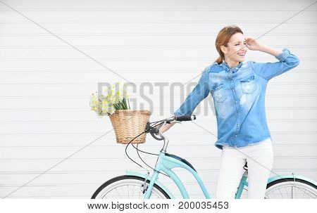 Young beautiful girl with bicycle and basket of flowers, outdoors