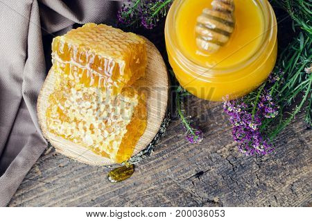 Honeycombs and glass pot with honey on old wooden table with purple flowers and place for text. Copy space. Top view.