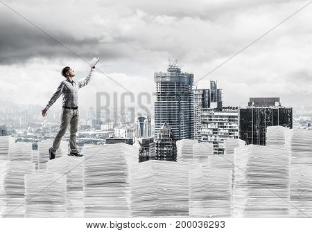 Young man in casual wear keeping hand with book up while standing on pile of documents with cityscape on background. Mixed media.