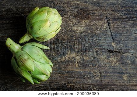 Two ripe fresh organic artichokes on rustic wooden background with place for text. Top view. Copy space.