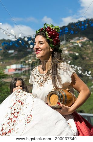 ESTREITO DE CAMARA DE LOBOS PORTUGAL - SEPTEMBER 10 2016: Woman wearing in traditional costume at Madeira Wine Festival in Estreito de Camara de Lobos Madeira Portugal. The Madeira Wine Festival honors the grape harvest with a celebration of traditional l