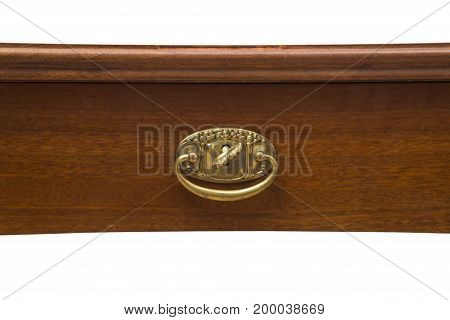Part of an antique wooden handcrafted table with gold metal handle on isolated white background