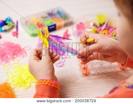 rubber, craft and fashion concept - Colored rubber bands for weaving accessories in the hands of a girl on a wooden background