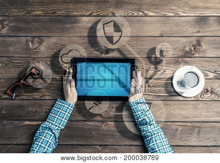 Top view of woman in checked shirt sitting at table with tablet device