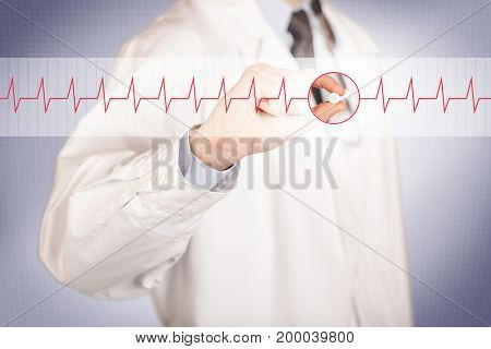 A male doctor in white coat with a stethoscope on one shoulder holding a pill between his fingers focused on a heartbeat graph