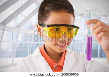 Schoolboy looking at test tube against modern room overlooking city