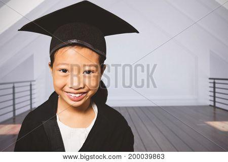 Portrait of smiling girl wearing mortarboard against white room