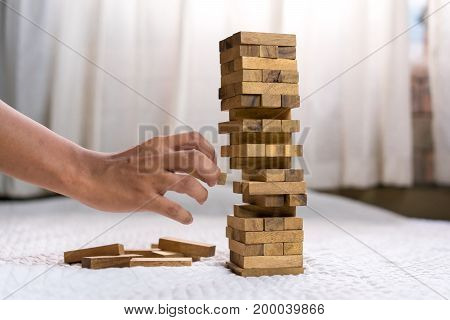 Young man pulling out wood block fail on building tower at home and drape change choice business risking dangerous project plan failure construction concept.