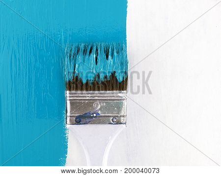 close up paint brush painting blue color on white wooden wall, renovate and decorate old house