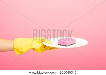 Hands in yellow protective gloves and a plate against rose background. cleaning concept