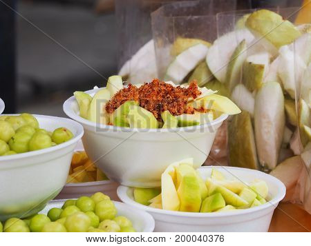 Raw Mango With Thai Dipping sauce Thai Fruits On White Plate Green Mango with Thai Dipping Sugar Salt and Chili