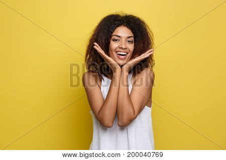 Smiling beautiful young African American woman in white T-shirt posing with hands on chin. Studio shot on Yellow background. Copy Space.