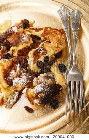 warm kaiserschmarrn with raisins and powdered sugar on a gold colored plate