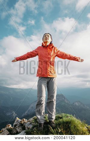 Happy traveler explorer young woman standing on peak of mountain with raised arms in summer.