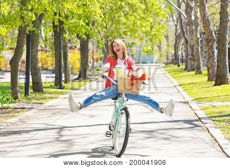 Young beautiful girl riding bicycle in park on sunny day