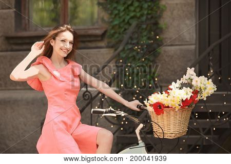 Young beautiful girl riding bicycle with flowers in basket on city street