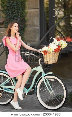 Young beautiful girl in dress with bicycle on city street