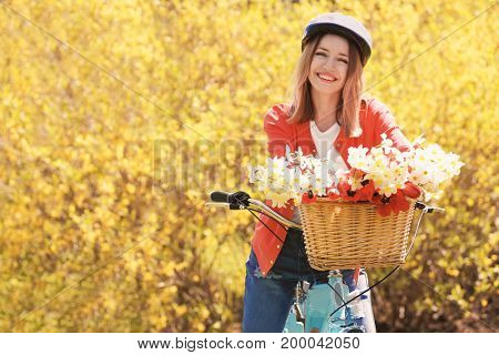 Young beautiful girl and bicycle with flowers in basket on blurred background