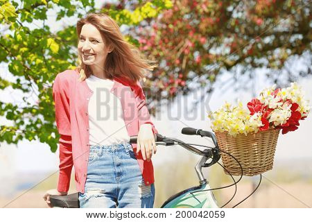 Young beautiful girl near bicycle with flowers in basket at park on sunny day